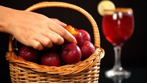 Female's hand keeping a half-eaten ripe plum with the other fruits in the basket - Indian summer fruit