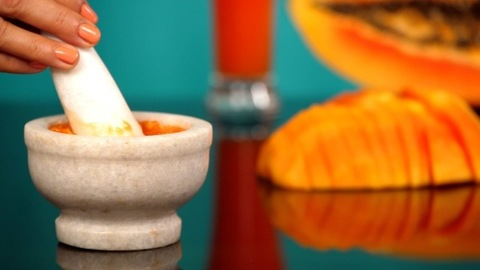 Female hands grinding the orange papaya in a mortar pestle to make a recipe