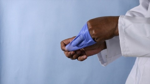 Male hands of a doctor removing his gloves after completing a successful surgery