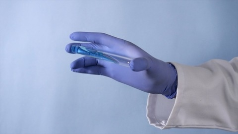 Health worker's hand with a test tube and researching medicine for the treatment
