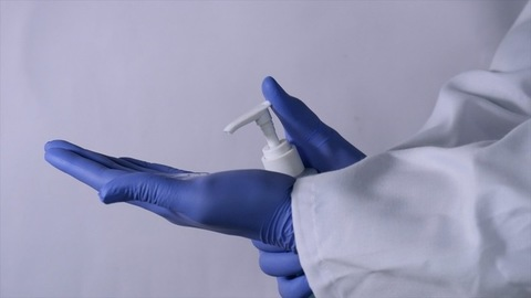 A senior doctor pouring sanitizer on his gloved hands for hygiene before patient treatment