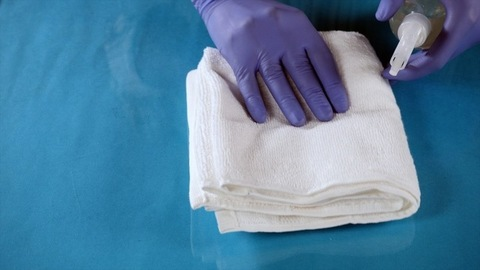 A medical worker disinfecting his work area using a white cloth and sanitizer