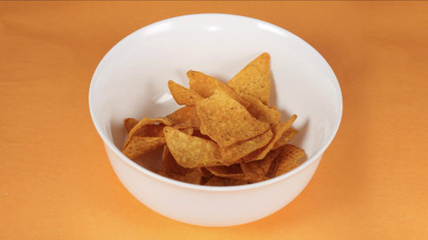 Stop motion shot of triangle-shaped chips / wafers kept in a container -  Time lapse shot