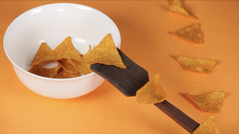 Stop motion shot of crunchy tortilla chips put in a container using a wooden spatula - Time lapse shot