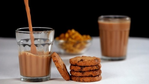 Freshly prepared hot tea served with crunchy and delicious biscuits for breakfast - Indian Chai