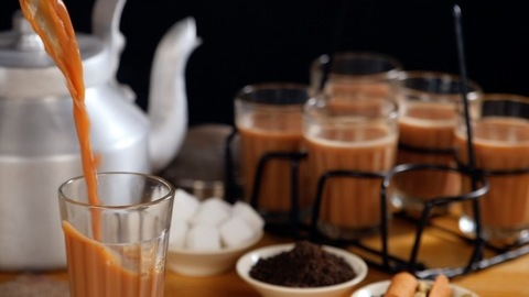 Boiling hot flavored tea pouring in transparent glass - refreshing hot  drink, Indian Chai