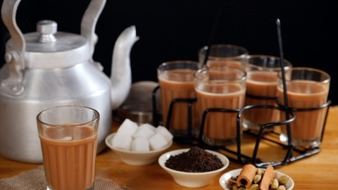 Smoke coming out of a glass of flavored tea kept on a jute mat with a kettle - Indian Chai