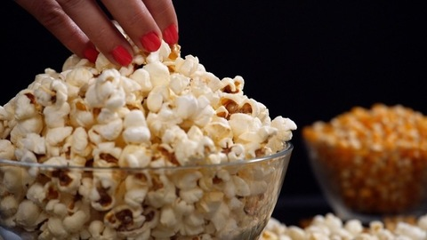 Beautiful hand of a female taking a few delicious popcorns from a container