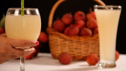 Female hand keeping a glass of fresh Litchi juice with a bunch of Lychees