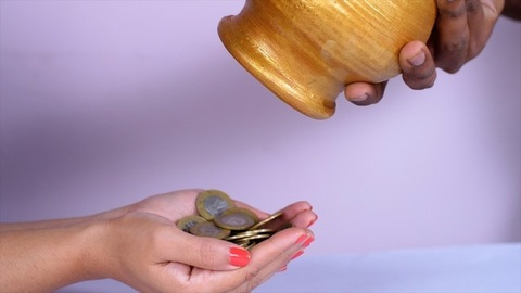 A stack of golden coins falling out in a heap from a jar / piggy bank - banking and finance