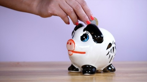 Female hand putting a coin inside her piggy bank - savings and investment