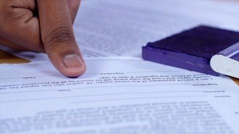 Male hand putting his thumb impression on legally approved bank papers / documents