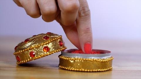 Female hands taking a bit of vermilion / Sindoor to celebrate an auspicious occasion