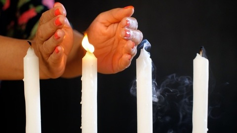 Female hand protecting one white candle from blowing out against the wind