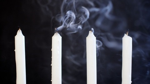 Extinct wax candle kept against a dark background - end of sorrow and sadness