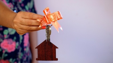 Female hands showing the keys of her new house decorated with a ribbon
