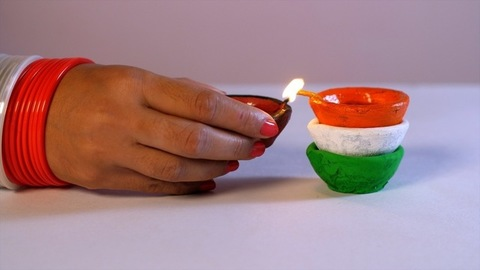 A woman with orange and white bangles lighting tricolor Diyas on Independence Day / Republic Day