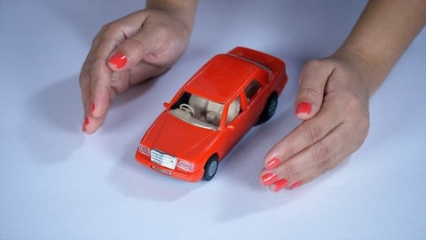 Woman's hand protecting her dream car against collision and damages - car insurance