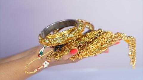 Indian woman holding beautiful gold jewelry - fashion and style