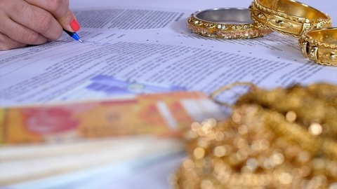 Female signing gold loan agreement against her gold jewelry - financial planning