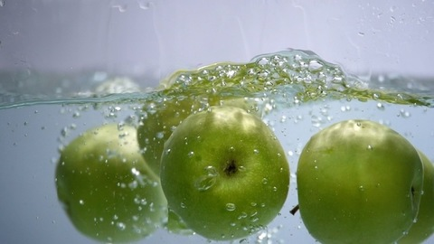 Ripe green apples falling down into clear water with splashes against a white background