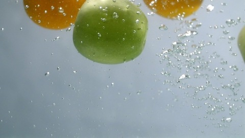 Whole green apples and yellow unpeeled oranges dropping in transparent water