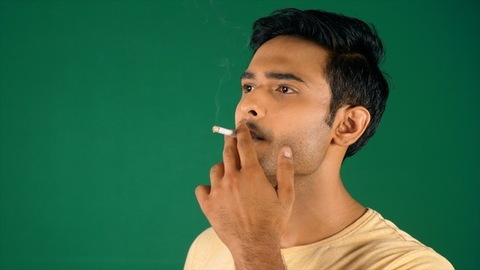 A young student in a yellow T-shirt smoking a cigarette - modern lifestyle