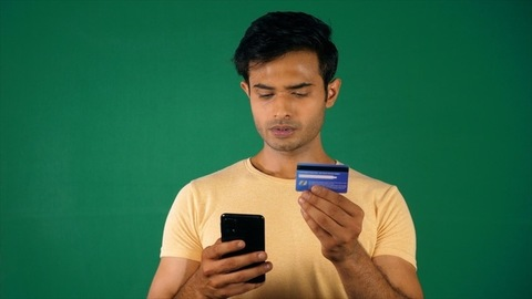 A young man - Online shopping using debit / credit card using his mobile. Chroma Green Screen
