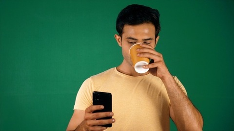 A smart Indian guy scrolling / browsing his smartphone. Green screen / Chroma shoot