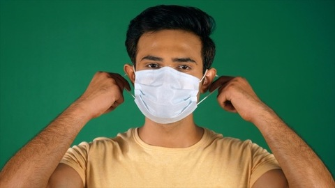 Portrait of a young guy taking off his medical mask - COVID