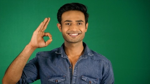 An attractive guy in his thirties showing the Ok super sign. Green screen / Chroma shoot