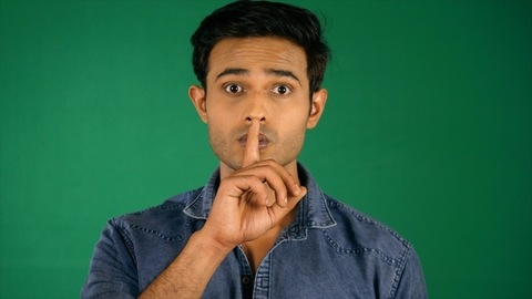 A young man with stubble in a blue shirt putting finger to his lips. Green screen / Chroma shoot