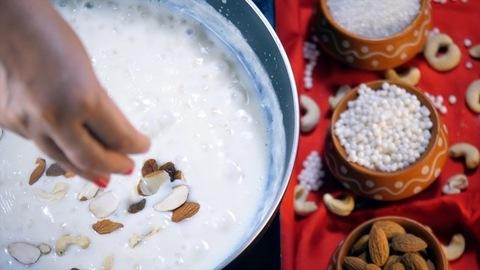 Woman's hand adding almonds, cashew nuts, and raisins into the Sabudana Kheer