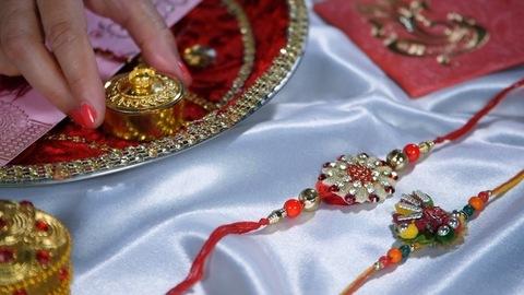 Female hand keeping a box of Kumkum / Tika on a Puja Thali on Raksha bandhan festival