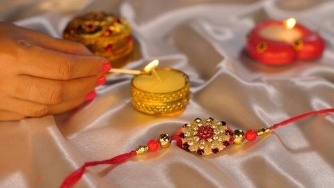 An Indian woman lighting a beautiful Diya on the occasion of Raksha Bandhan - Rakhi, Hindu Festival