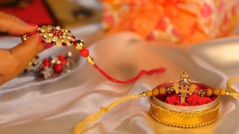 Female hand take a beautiful Rakhi for tying on her brother's wrist - Hindu festival