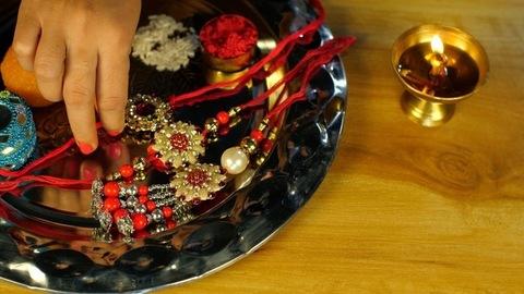Female's hand taking a few rice grains, Tika and a Rakhi from a religious Puja Thali - Rakhi, Hindu Festival