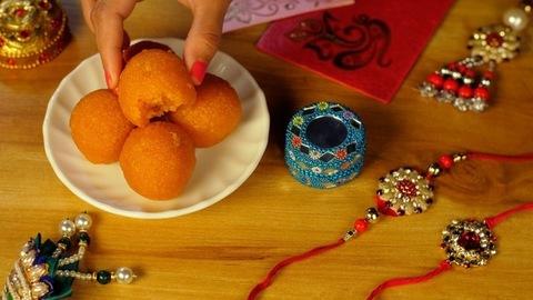 A lady is eating an Indian traditional sweet / Laddu on Raksha Bandhan festival