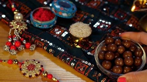 Female hand keeping a bowl of chocolates with a burning Diya on Raksha Bandhan