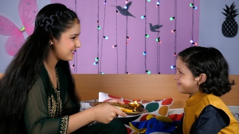 Cheerful elder sister with a Puja Thali in her hands blessing her brother - Raksha Bandhan Indian Festival