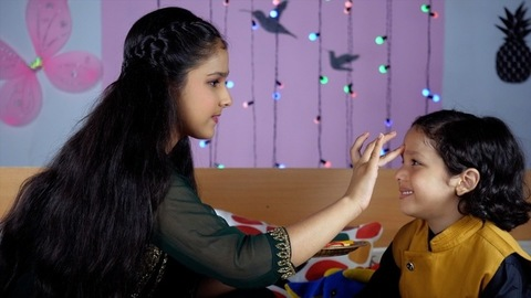 An Indian girl happily applying Tika / Tilak on her brother's forehead on the occasion of Rakhi