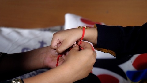 Pretty sister tying Rakhi on her brother's wrist as a symbol of love, care, and respect
