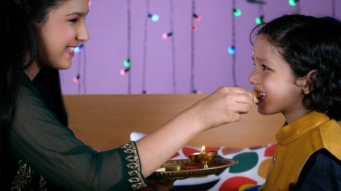 A beautiful sister offering sweets to her sweet little brother on the festival of Rakhi