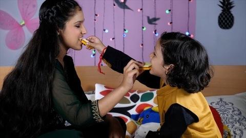 Cheerful young siblings eating sweets celebrating the festival of Rakhi at home - Raksha Bandhan Indian Festival