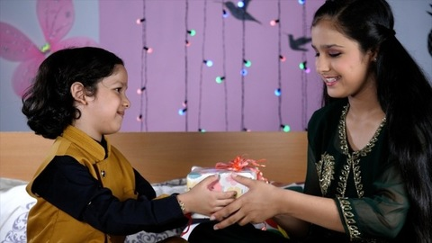An adorable little child giving a colorful gift to his sister on the Rakhi festival