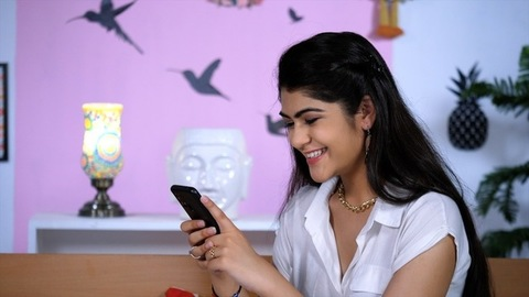 A cheerful young woman holding a mobile - online chatting, mobile use