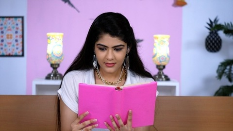 A pretty college student reading an interesting storybook in her leisure time