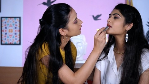 Pretty teenage girl doing makeup for her best friend getting ready for a party