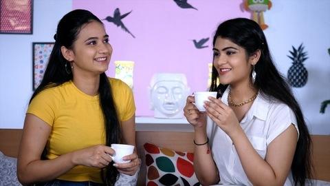 Two pretty college-going teens enjoying a hot cup of tea / coffee - Gossip, Friends talking