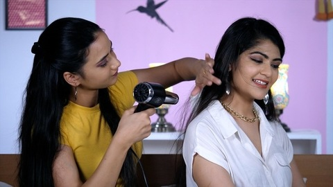 A young beautician blow-drying her client's hair after a haircut - occupation and profession